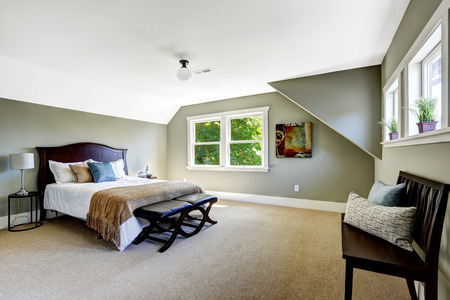bedroom design: Bedroom interior with beige carpet floor and green walls. Furnished with wooden bed and  bench