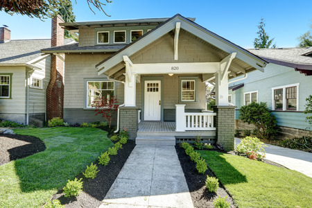 american house: House entrance porch with white wooden door and white railings. Front yard lansdcape with walkway