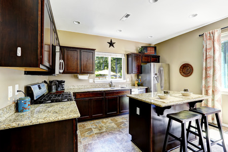 kitchen island: Dark brown cabinets with granite tops. Kitchen island with stools