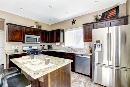 brown granite: Dark brown cabinets with granite tops. Kitchen island with stools