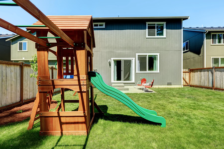 land slide: Fenced backyard with wooden playground for kids