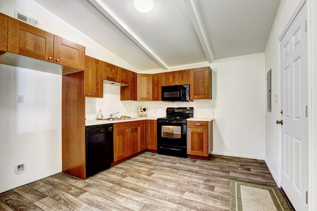 black appliances: Mother in law kitchen room inteior. Bright room with wooden cabinets and black appliances