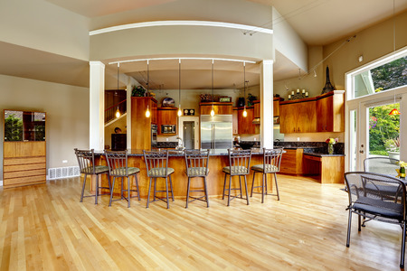 granite kitchen: Spacious luxury kitchen room with columns and round granite counter top with stools Stock Photo