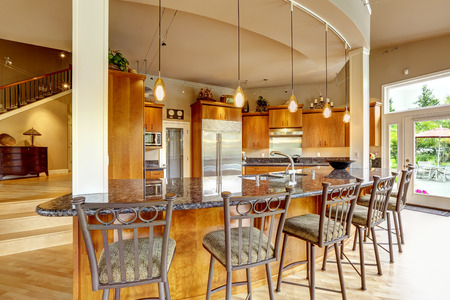 home appliances: Spacious luxury kitchen room with columns and round granite counter top with stools Stock Photo