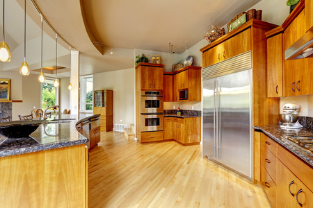 kitchen appliances: Spacious luxury kitchen room with round granite counter top and steel appliances