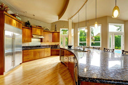 black appliances: Spacious luxury kitchen room with round kitchen island and black granite tops