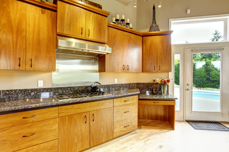 kitchen cabinets: Luxury kitchen room with honey wooden cabinets and black granite tops Stock Photo