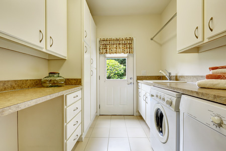 cabinets: Bright laundry room with white cabinets and appliances