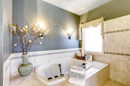 Bathroom with bath tub, tile trim and contrast green and lavender walls
