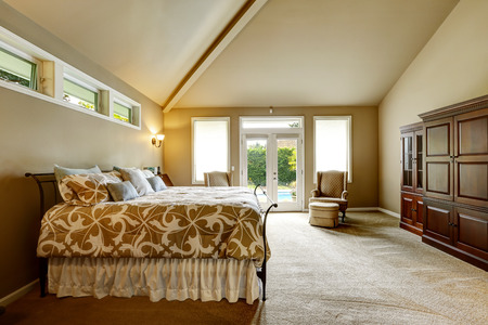 vaulted: Luxury bedroom interior in soft beige color with beautiful bed, wardrobe. Room with high vaulted ceiling and walkout deck