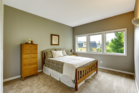 Bedroom interior in grey color with wooden bed, nightstand and dresser photo