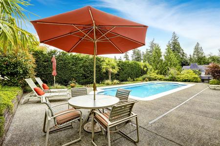 Achtertuin met zwembad, ligstoelen en een patio tafel met parasol