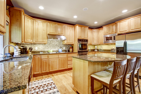 Light brown kitchen room with granite tops and kitchen island. Tile backspash trim photo