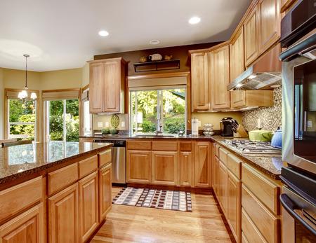 splash back: Light brown kitchen room with granite tops and kitchen island. Tile backspash trim