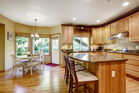granite kitchen: Light brown kitchen room with granite tops and kitchen island. Tile backspash trim. Kitchen with dining area Stock Photo