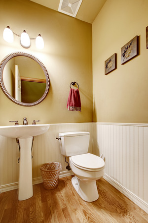 white trim: Small bathroom with white washbasin stand and toilet.  Beige wall with white trim