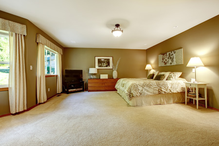 bedroom: Spacious warm bedroom interior with brown walls and ivory bed