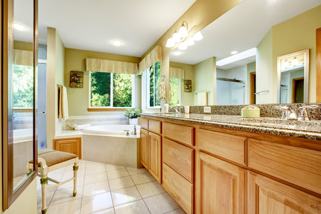 corner tub: Bright bathroom with corner bath tub , cabinet with granite top and large mirror