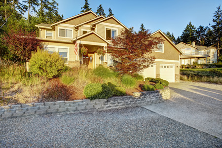 driveways: American architecture. House with clapboard siding and stone trim. View of fornt yard landscape and driveway Stock Photo