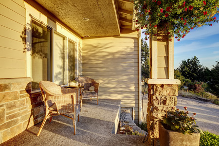 front porch: Entrance porch with wicker chairs. Porch with stone trim  decorated with flowers Stock Photo