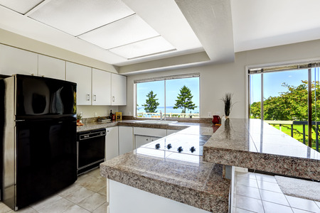 White kitchen room with black appliances and granite tops.  Kitchen with walkout deck