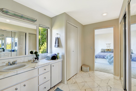 master bath: White bedroom interior with tile floor and white cabinets