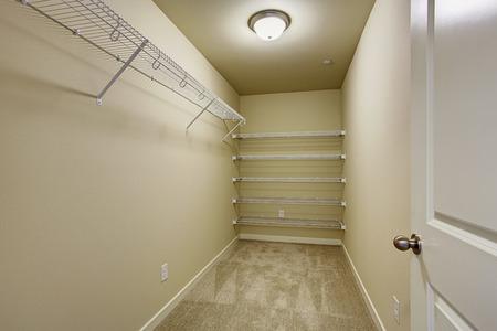 Empty narrow walk-in closet with shelves Stock Photo