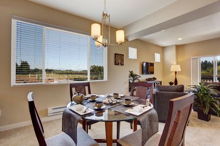 open floor plan: Modern apartment interior with open floor plan. DIning area with served round table and chairs