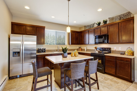 Modern kitchen room with kitchen island and stools.  Dark brown cabinets, steel appliances and tile floor Stock Photo