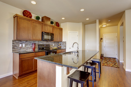 back kitchen: Bright house interior. Kitchen room with granite tops, island with stools Stock Photo