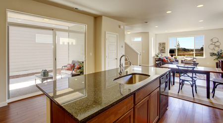 kitchen island: Bright house interior. Kitchen room with kitchen island and walkout deck