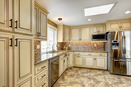 Luxury kitchen interior in light beige color with back splash trim and tile floor Stock Photo