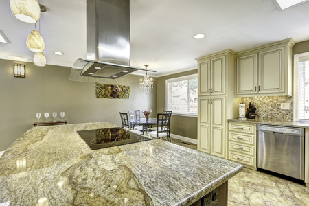 to the top: Spacious kitchen room with tile floor. Big kitchen island with built-in stove, granite top and steel hood