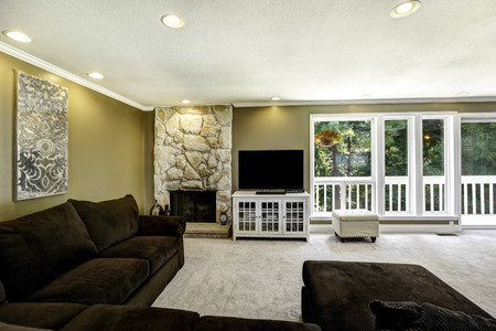 stone  fireplace: Room with comfortable brown sofa, stone trim fireplace and tv