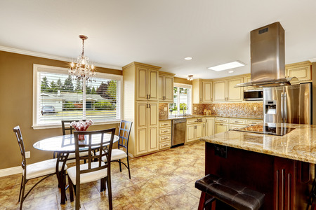 back kitchen: Spacious kitchen room with tile back spash trim and tile floor. Big kitchen island with built-in stove, granite top and steel hood. DIning area