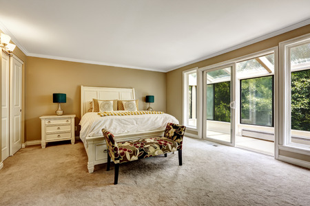 screened: Bright bedroom with carved wood bed, colorful ottoman and walkout screened deck Stock Photo