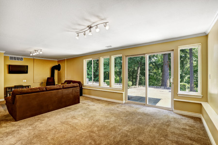 glass doors: Bright room with brown sofa and exit to backyard