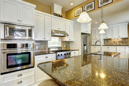 appliances: Bright kitchen room with granite tops, kitchen island and white cabinets Stock Photo
