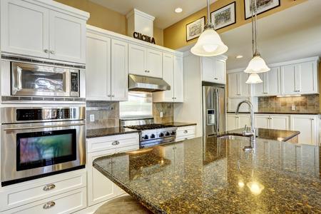 cuisine fond blanc: Salle de cuisine lumineuse avec des sommets de granit, �lot de cuisine et des armoires blanches