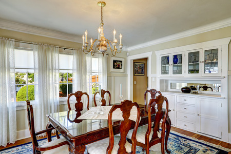 Bright dining room with rich carved wood dining table set and white storage cabinets photo