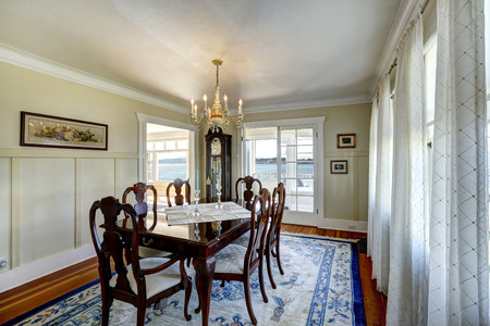 grandfather clock: Bright dining room with rich carved wood dining table set and antique grandfather clock