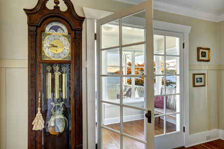 french doors: Antique carved wood grandfather clock in dininig room. Stock Photo