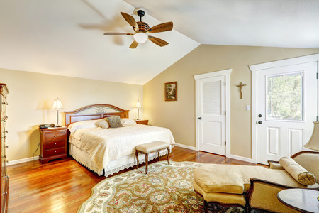 vaulted: Warm tones bedroom interior with vaulted ceiling and hardwood floor. Room furnished with antique  chari, ottoman and bed Stock Photo