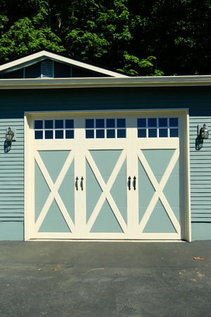 white trim: Siding garage with door and white trim. Wall decorated with lanterns