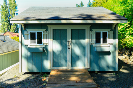 white trim: Wooden shed with small windows and white trim