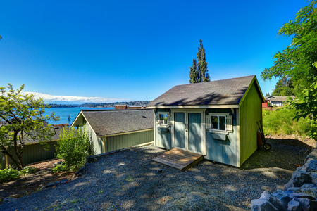 white trim: Wooden shed with small windows and white trim on backyard overlooking bay. Port Orchard town, WA Stock Photo