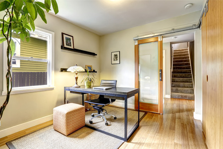 office desk: Bright office room interior with tree. Simple black wooden desk with whirlpool chair