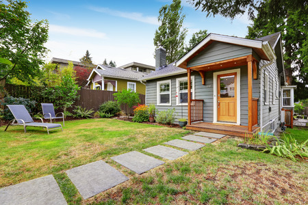 Small grey house with wooden deck. Front yard with deck chairs and flower bed photo