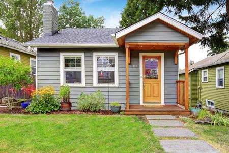 exteriores: Pequeña casa gris con cubierta de madera. Patio delantero con cama de flores y el césped Foto de archivo