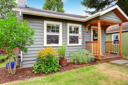 Small grey house with wooden deck. Front yard with flower bed and lawn photo